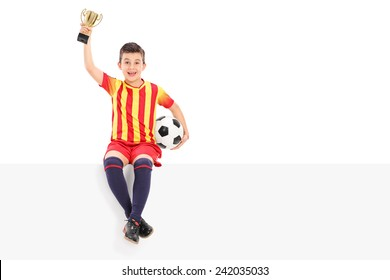 Junior football player holding a trophy on a panel isolated on white background