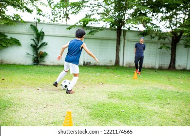 Junior football player prepare and play soccer together.Asian kids playing.