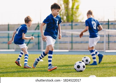 Junior Football Players Making Sports Training, Happy Boys on Soccer Practice Session on Summer Time. School Sports Stadium in the Background