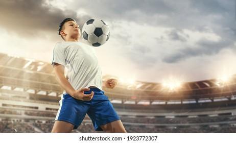 Junior-Fußball oder Fußball-Spieler im Stadion in Taschenlampe. Junge männliche sportliche Modellausbildung. Moment des Angriffs, des Fangs. Konzept von Sport, Wettbewerb, Gewinnen, Action, Bewegung, Überwindung.