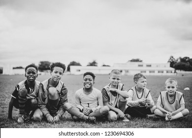Junior football team sitting on the grass