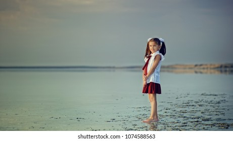 Junior girl in school uniform standing on water happy about holidays end. Back to school concept