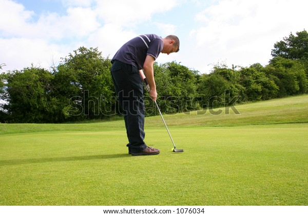 A junior golf champion putts in for a birdie