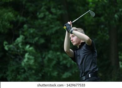 A junior golf hits a golf shot