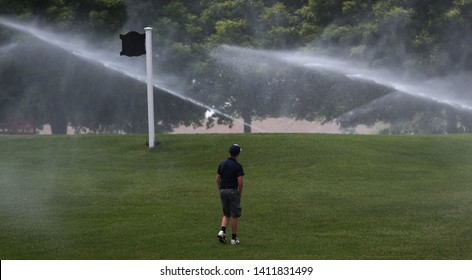 A junior golfer cools off by standing in the mist of a golf course water sprinkler