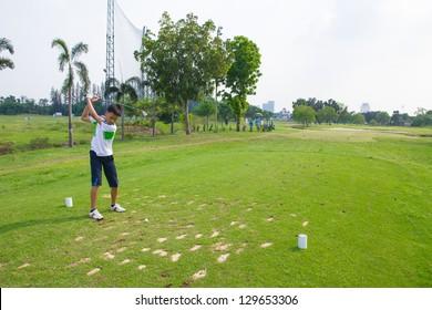 Junior golfer driving golf ball on golf course