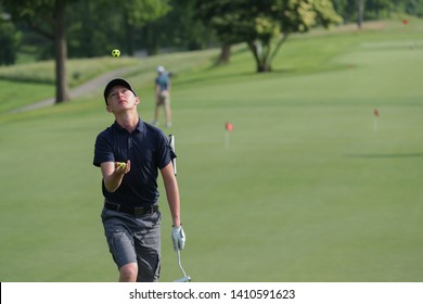 A junior golfer juggles golf balls just prior to competing in a match