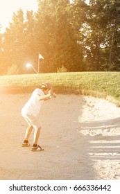 JUNIOR GOLFER MAKING A NICE DOWN SWING IN A SAND TRAP WITH SUNSET LIGHT