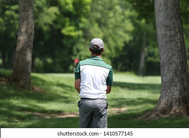 A junior golfer prepares to hit a shot between two trees