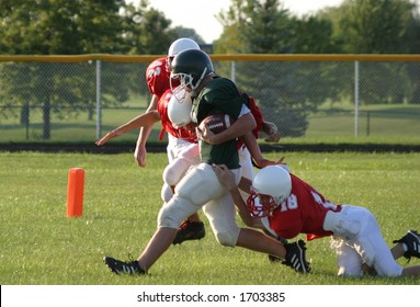 Junior high football players running a play.