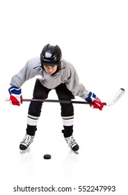 Junior ice hockey player with full equipment and uniform isolated on white background. In faceoff stance with hockey puck.