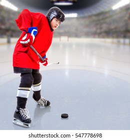 Junior ice hockey player handling puck on ice with arena full of fans in the stands and copy space. Focus on player and deliberate shallow depth of field on background.