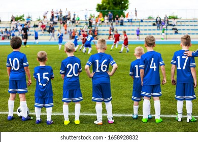 Junior Level Kids Sports Team. Football Soccer Children Players Standing Together with Coach During School Soccer Competition Game. Boys in Blue Soccer Jersey Sportswear and Soccer Cleats