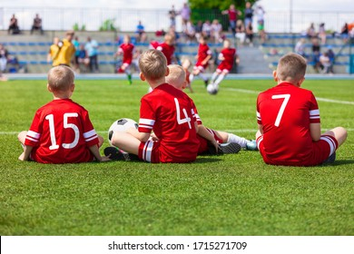 Junior Level Kids Sports Team Sitting on Grass Field. Football Soccer Children Players Standing Together During School Soccer Competition Game. Boys in Red Soccer Jersey Sportswear and Soccer Cleats