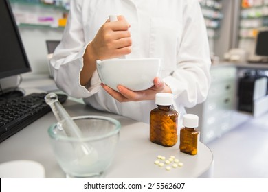 Junior pharmacist mixing a medicine at the hospital pharmacy