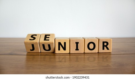 From junior to senior symbol. Turned cubes and changed the word 'junior' to 'senior'. Beautiful wooden table, white background, copy space. Business and junior or senior concept.