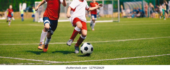 Junior Soccer Match. Football Game For Youth Players. Boys Playing Soccer Match on Football Pitch. Football Stadium and Grassy Field in the Background
