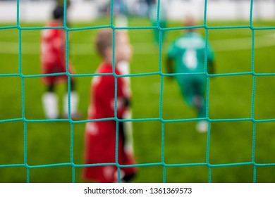 Junior Sports Soccer Background. Soccer Goal Net and Blurred Youth Players in the Background