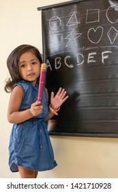 Junior teacher teaching alphabets with fun, little indian girl teaching abcd