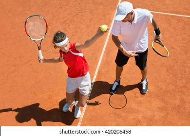 Junior tennis player practicing service with tennis coach
