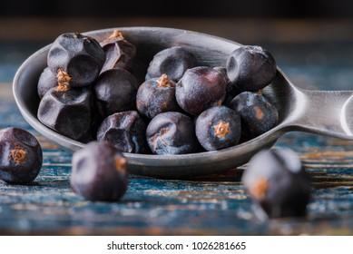 Juniper berries spilling from a teaspoon