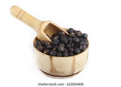 juniper berries in wooden cup isolated