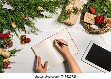 Juniper branches with a Christmas decor. Christmas, New Year background. Coniferous branches of juniper, notepad and white tablet with black screen. Top view, flat design.