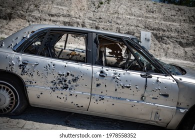 Junk cars with bullet holes and  bullets inside.