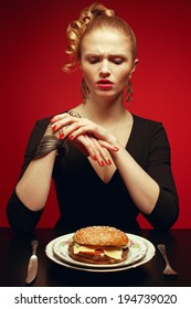 Junk food concept. Portrait of unhappy luxurious red-haired model in black cocktail dress trying to eat burger. Perfect hair, skin, make-up and manicure. Golden accessories. Studio shot