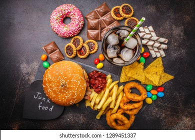 Junk food concept. Unhealthy food background. Fast food and sugar. Burger, sweets, chips, chocolate, donuts, soda on a dark background.