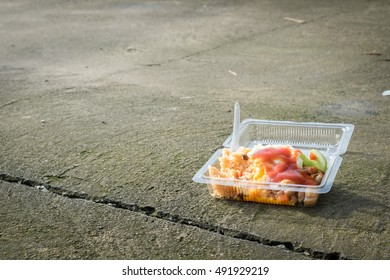 Junk food, fried rice, fried egg and sausage in plastic box on the floor.