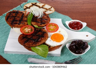 junk food meat big beef hamburger fried eggs on white  wood plate with cutlery ketchup sauce and pickels on blue mat over wooden table