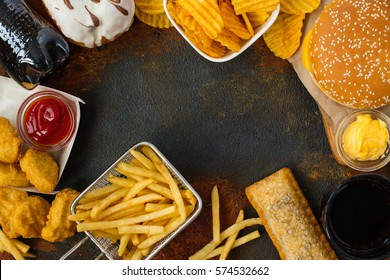 Junk food on table. Fast carbohydrates not good for health, heart and skin. Space for text