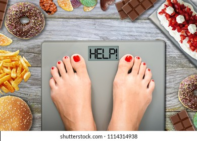 Junk food or sugar sweets temptations when you diet concept with feet on weight scale