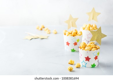 Junk sweet food concept. Portion of caramel popcorn in paper glasses boxes ready for party holidays and cinema. Copy space background