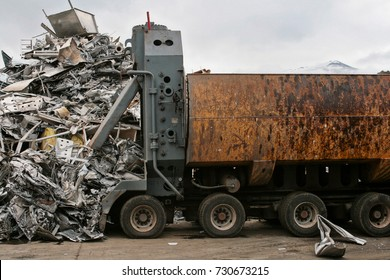 Junk truck with a mountain of scrap metal in a scrapyard. With a background of snowy mountain and cloudy day.