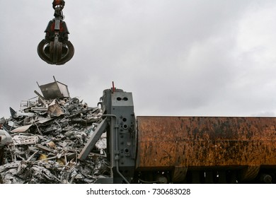 Junk truck with a mountain of scrap metal in a junkyard. On a cloudy day.