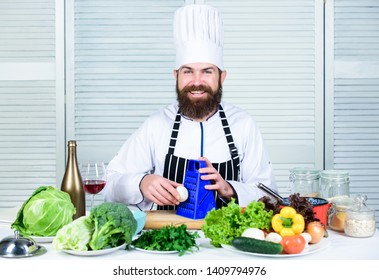 Junk versus healthy. Chef man in hat. Secret taste recipe. Dieting and organic food, vitamin. Healthy food cooking. Vegetarian. Mature chef with beard. Bearded man cook in kitchen, culinary.