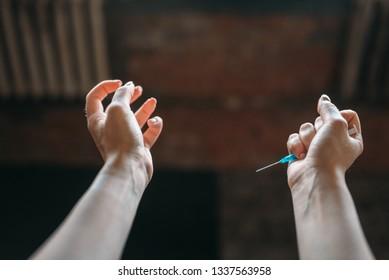 Junkie hands with syringe, drug addiction concept