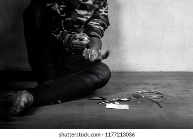 Junkie man holding drug syringe injection heroin to hand.Social disaster and epidemic of narcotic addiction concept.Free space.