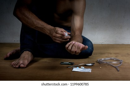 Junkie man holding drug syringe injection heroin to hand.Social disaster and epidemic of narcotic addiction concept.