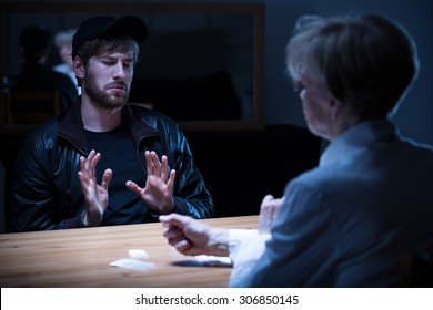 Junkie man interrogated by policewoman in a dark room