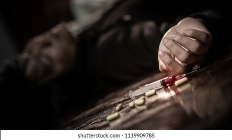 Junkie man lying on the fllor near drug injection syringe and pills. Death from drug overdose and addiction concept
