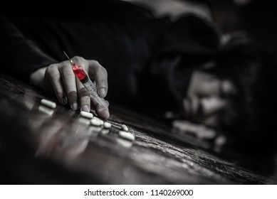 Junkie man lying on the floor while holding drug injection syringe and pills. Death from drug overdose and addiction concept