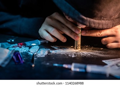 Junkie man taking heroin, cocaine or other narcotic substance by using bank note. Drug abuse and addiction concept