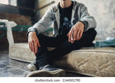 Junkie sitting on the mattress and smoke cigarette