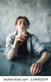 Junkie sitting at the table with syringe in hand