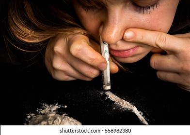 Junkie woman snorting cocaine powder with rolled banknote on black background