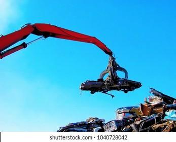 Junkyard crane with claw moving crushed car