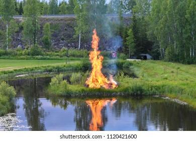 Juokslahti, Finland - June 23 2018: The traditional midsummer bonfire burning  at the center of a small beach in Majatalo Morva.